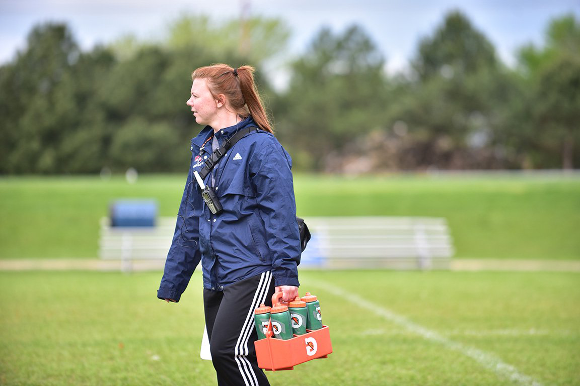 Athletic trainer delivers water to the football field